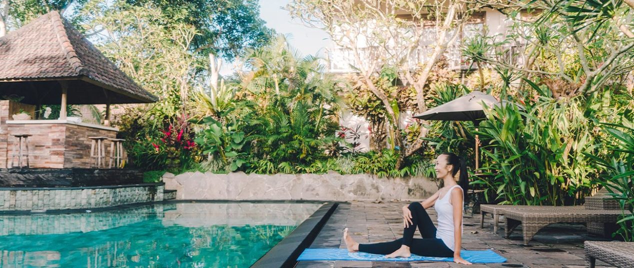 woman by villa pool doing yoga